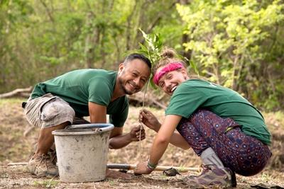 Conservation volunteer plants native tree species with staff member in Barra Honda National Park