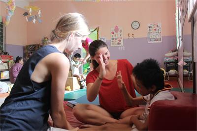 Projects Abroad physiotherapy volunteer from Australia works with a child at a placement in Cambodia