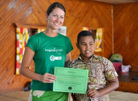 Projects Abroad Care volunteer hands over a certificate of participation to a boy at the Fiji Holiday School graduation