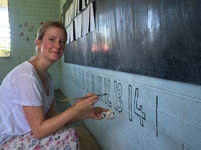 Care & Community Alternative Schoolies volunteer painting numbers on a wall