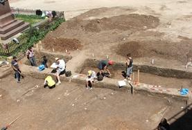 Archaeology volunteers work together on an excavation during their internship in Romania.