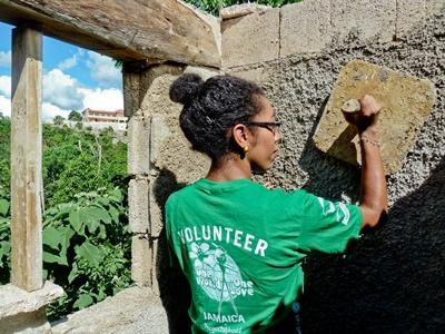 A female volunteer helps plaster a wall in a building project in Jamaica