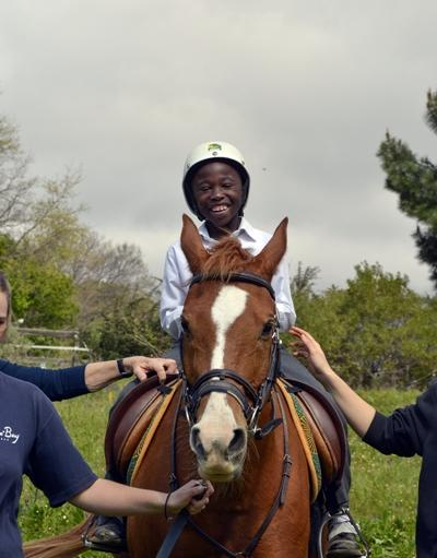 A young child smiles on horseback at a Projects Abroad equine therapy placement in South Africa