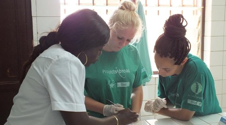 Two volunteers working alongside a local medical staff member during an HIV testing outreach session