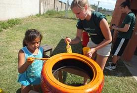 A childcare volunteer and a local child work together to paint a tyre to be repurposed for a playground in Argentina.