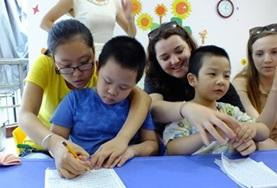Childcare volunteers work closely with children from a kindergarten in China, helping them to draw and colour in.