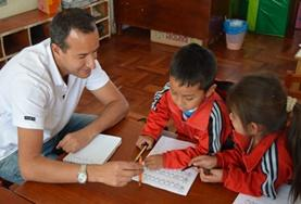 A volunteer provides support for children as they finish their homework at one of our childcare placements at a school in Peru.