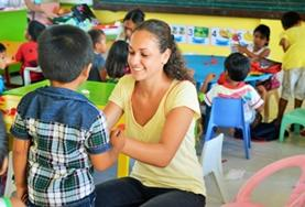 A volunteer plays an interactive game with a young boy at one of our childcare placements in the Philippines.