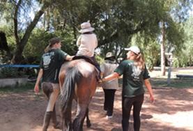 Two Equine Therapy volunteers support a child during a treatment session at our Care placement in Bolivia.