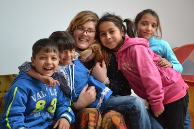 Female Projects Abrpad volunteer with a group of children at a care placement in Romania, Europe