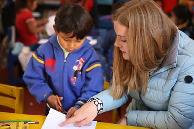 Projects Abroad Care volunteer overseas in Peru explains to young child how to cut using scissors