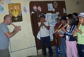 A Music volunteer teaches a local child how to play wind instruments during a music therapy session in Bolivia.