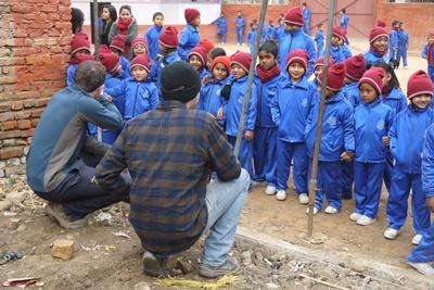 Male volunteers meet school children at their new building on the Disaster Relief project in Nepal
