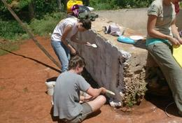 High School Project Building volunteers cover a brick wall with cement in a local community in Jamaica.