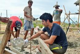 A High School Project volunteer helps with building the framework for a house in the Philippines.