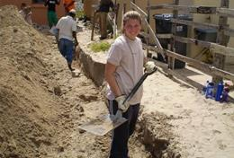 A High School Project Building volunteer assists with laying the foundation for a new house in South Africa.