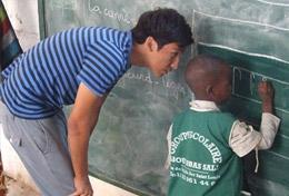A high school student teaches a child how to write on a blackboard at his volunteer placement at a school in Senegal.