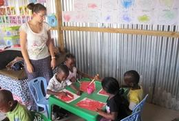A High School Project volunteer holds an art class to teach children at a daycare centre in South Africa how to paint.
