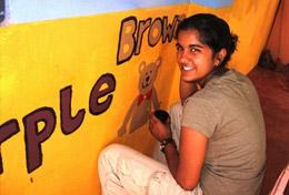 A High School Project volunteer paints an educational mural at a school as part of her Care & Community work in Sri Lanka.