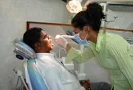 A high school student interning in Sri Lanka observes the work of a local dentist.