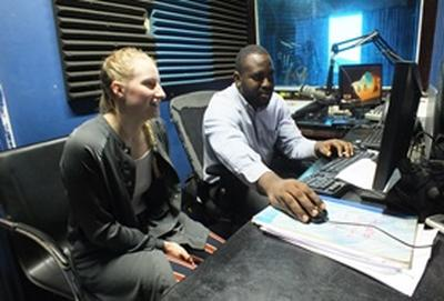 A Journalism intern works on a radio broadcast with a local radio DJ in Jamaica.