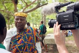 A Journalism intern conducts an interview with a man for a local news broadcasting company in Togo.