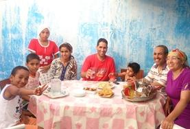 A volunteer practises his French skills with his host family after taking an intensive language course in Morocco.