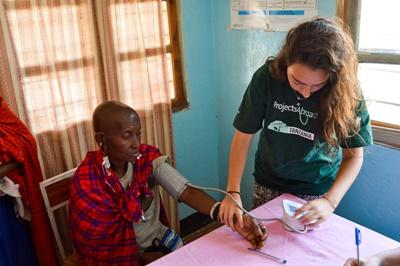 A female Projects Abroad Medical volunteer measuring the blood pressure of a Tanzanian local