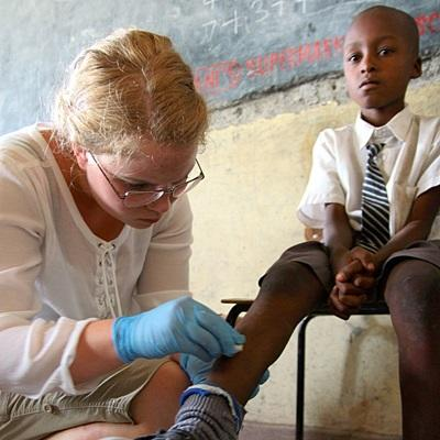 A medical volunteer concentrates as she helps a young child in Kenya.
