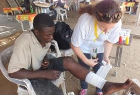 A Medicine volunteer assists with dressing a patient's wound during her internship in Togo.