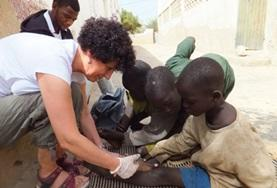 A Nursing volunteer assists local medical staff with dressing children's wounds at our medical placement in Senegal.