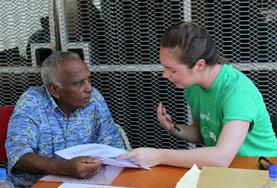 A Nutrition intern measures a man's blood sugar level during a diabetes awareness campaign at our volunteer placement in Fiji.