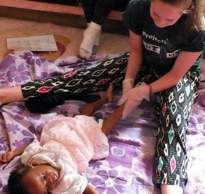 An occupational therapy volunteer helps a young girl move her legs in Kenya.