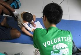 Under the guidance of a qualified occupational therapist, a medicine volunteer in the Philippines administers a test to determine the tasks that a disabled child is struggling with.