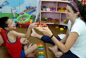 A volunteer Occupational Therapy intern works on a treatment activity with a disabled boy in Vietnam.