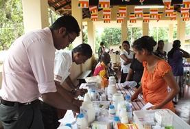 A Pharmacy intern shadows a local pharmacist as he dispenses medicine to local people in Sri Lanka.
