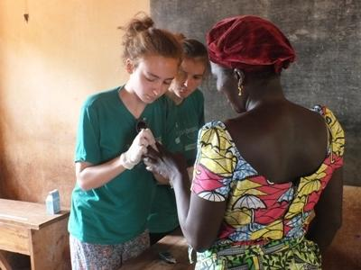 Two Projects Abroad volunteers conducting a diabetes test during a public health outreach in Togo