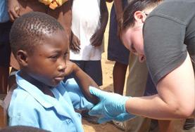 A Nursing volunteer cleans a child's wound as part of her medical internship abroad.
