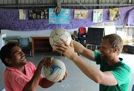 A Physiotherapy volunteer does light stretches with a boy at a care centre as part of one of our medical internships.