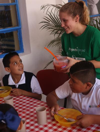 A Projects Abroad social work intern in Mexico serves salsa to children during breakfast
