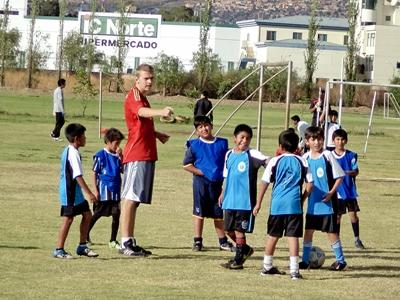 Young Bolivian children enjoy a soccer lesson with a Projects Abroad volunteer.