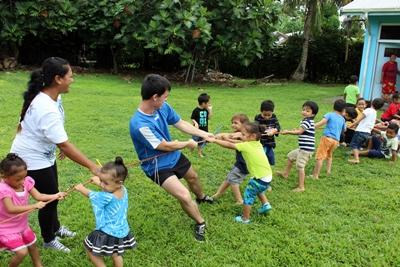 Projects Abroad Volunteers play a game of tug of war with small children in Samoa