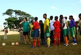 A volunteer coaches students through a soccer drill during a school sports lesson in Jamaica.