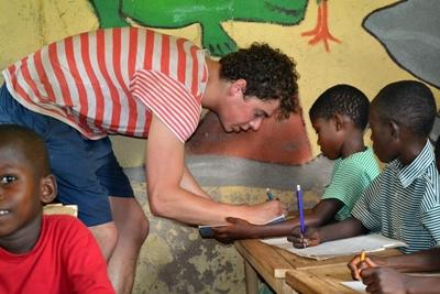 Projects Abroad volunteer helps children in Ghana with English reading and writing lessons.