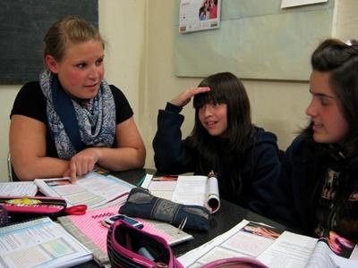 A Projects Abroad volunteer helps two of her students at a school in Argentina, Latin America.