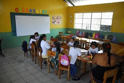 A volunteer sits with her class at a school in Ecuador, Latin America.