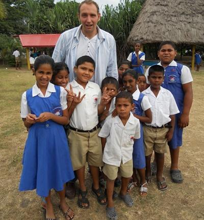 A volunteer poses with his students in Fiji, South Pacific.