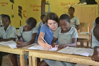 Projects Abroad Teaching volunteer Pascale Fortin helping a school girl at her teaching placement in Ghana
