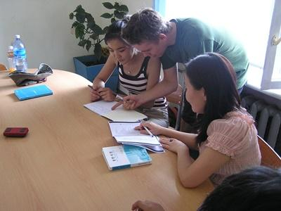 A volunteer helps his student with her homework in a classroom in Mongolia, Asia.