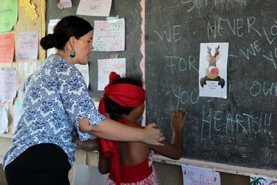 Projects Abroad Teaching volunteer with child at AH Mu Academy School in Samoa